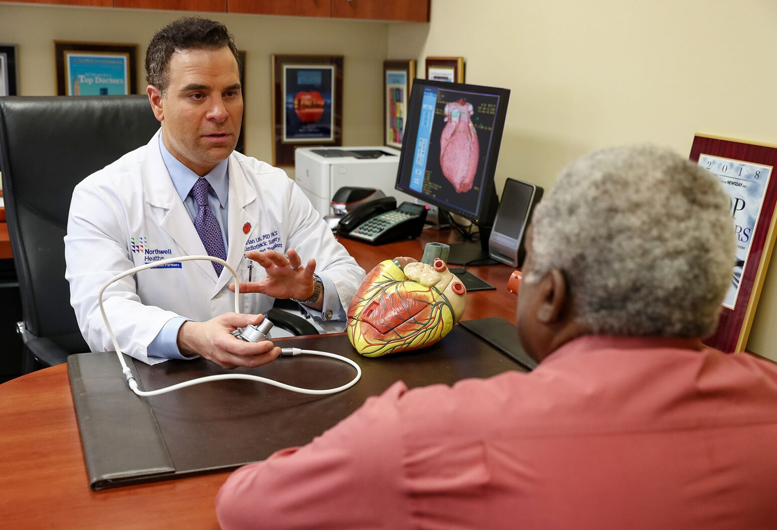Cardiothoracic surgeon Dr. Lima uses a model heart to show an older male patient how the VAD works