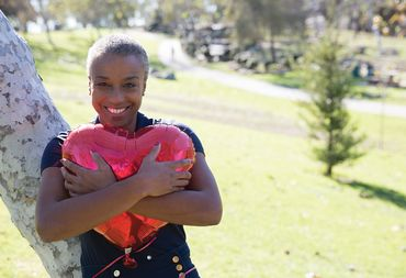 Smiling African-American woman stands against tree holding heart shaped balloon.