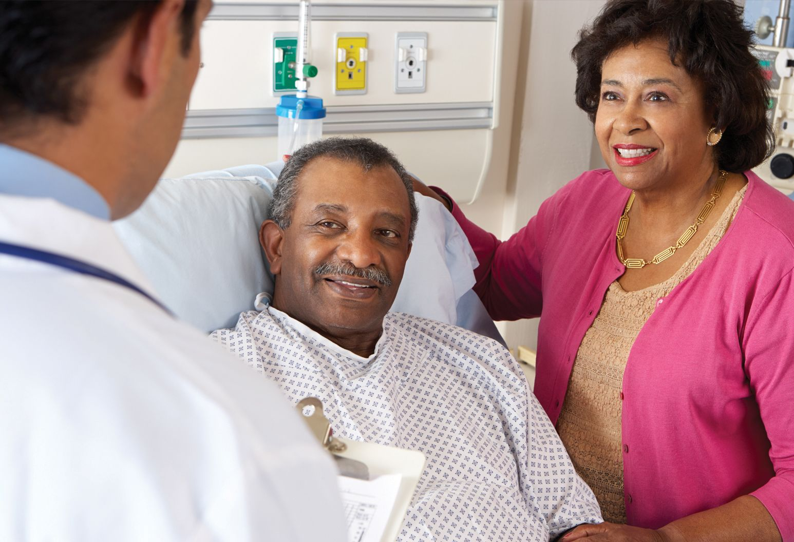 A black man sits in a hospital bed with his wife next to him