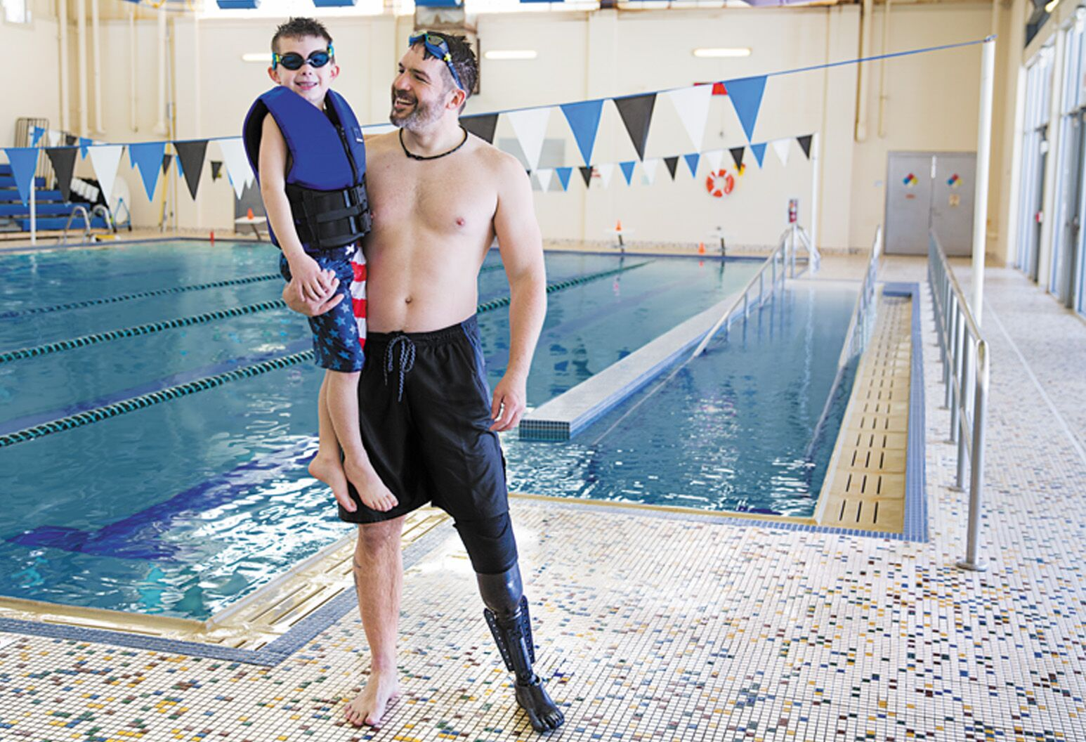 Dan Lasko holds his son after getting out of the water, wearing Northwell's The Fin.