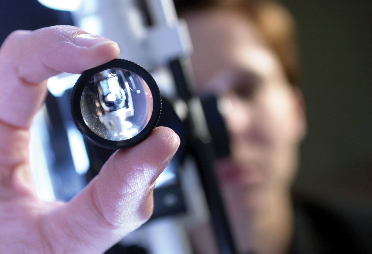 An ophthalmologist holds a lens closely