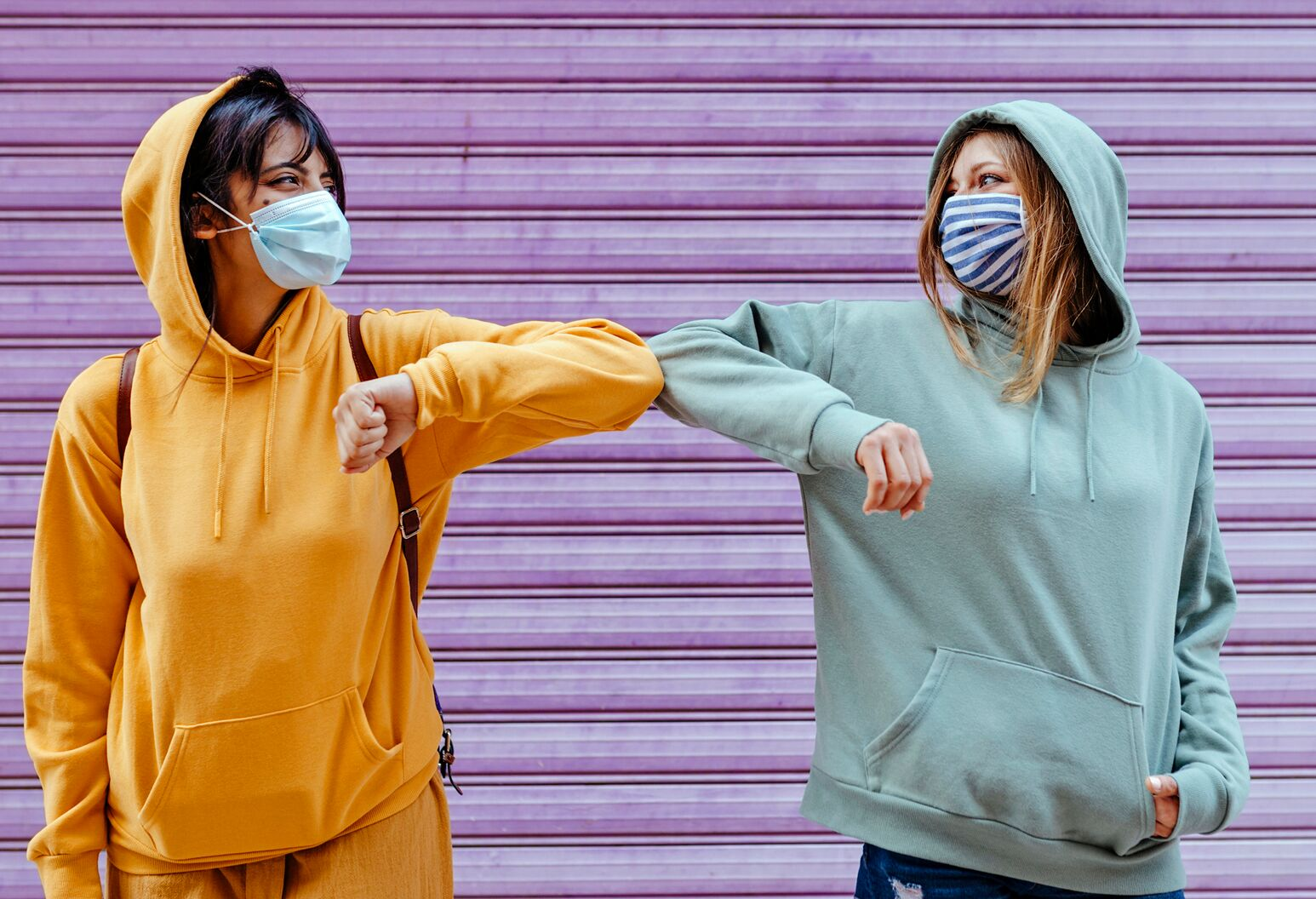 Two dark-haired young women in sweatshirts and masks happily bump elbows