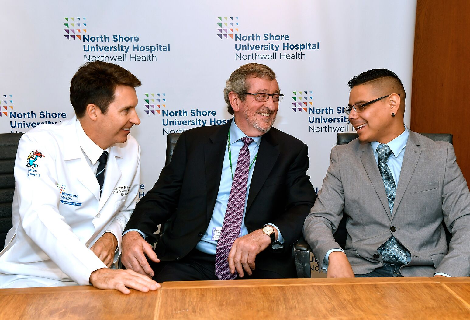 Luis Rios (right) and James Bradley, MD, talk with Michael Dowling during a press conference.