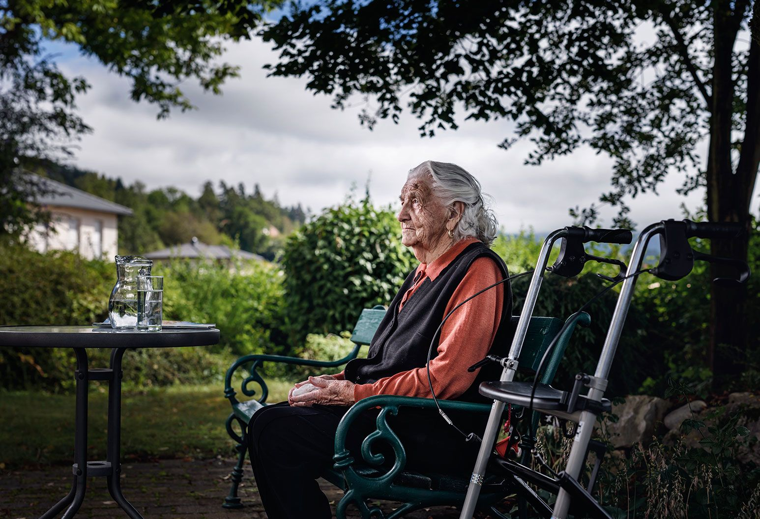 An elderly woman sits outside on a bench outside. She is wearing a orange shirt with a black vest over it and looks off into the distance. Beside her is her walker parked right next to he bench and on her other side is a table with a jug filled with water.