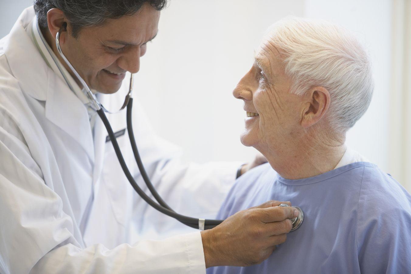A cardiologist checks an elderly man's heart