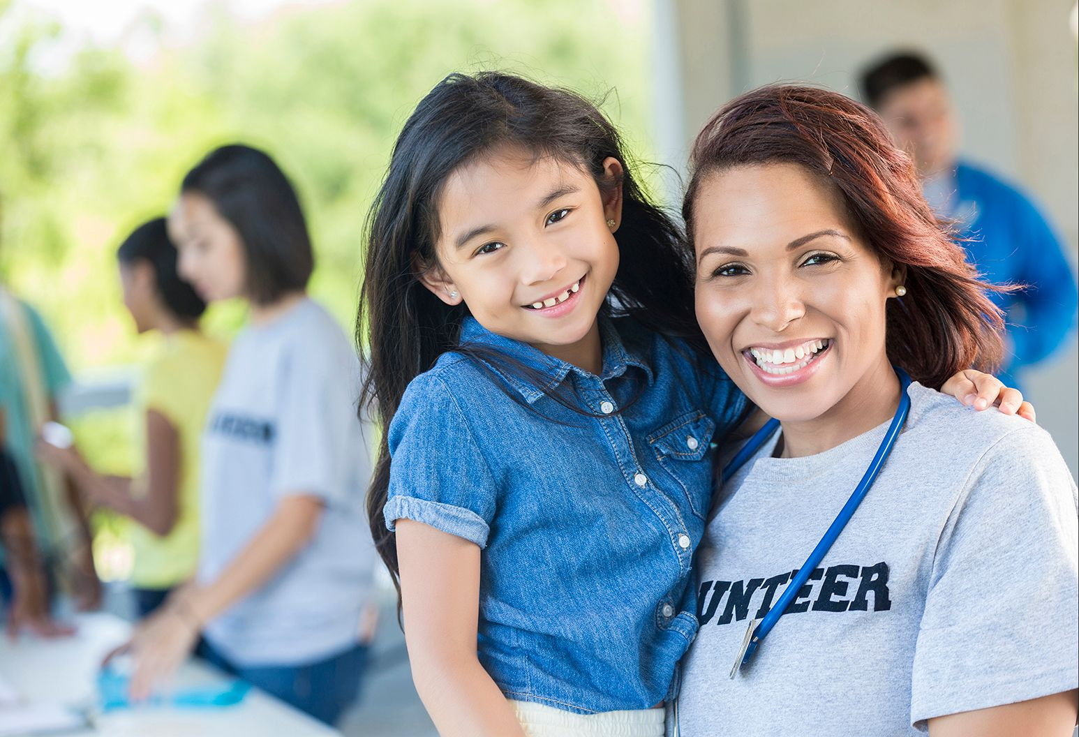 "Cheerful volunteer wearing a grey t-shirt that says ""volunteer"". She is holding on to the little girl. They are blissfully smiling at the camera. There are others working blurry behind them."