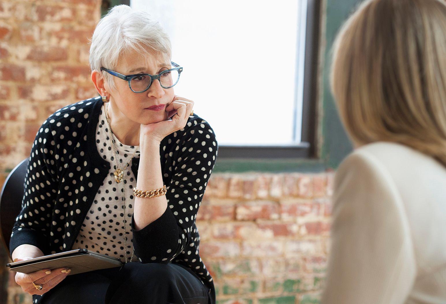 Caucasian businesswomen talking in office with digital tablet