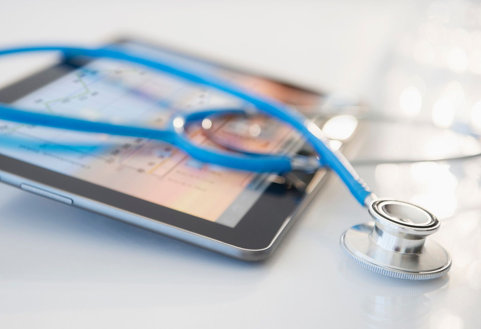 Blue stethoscope is shown over a computer tablet.
