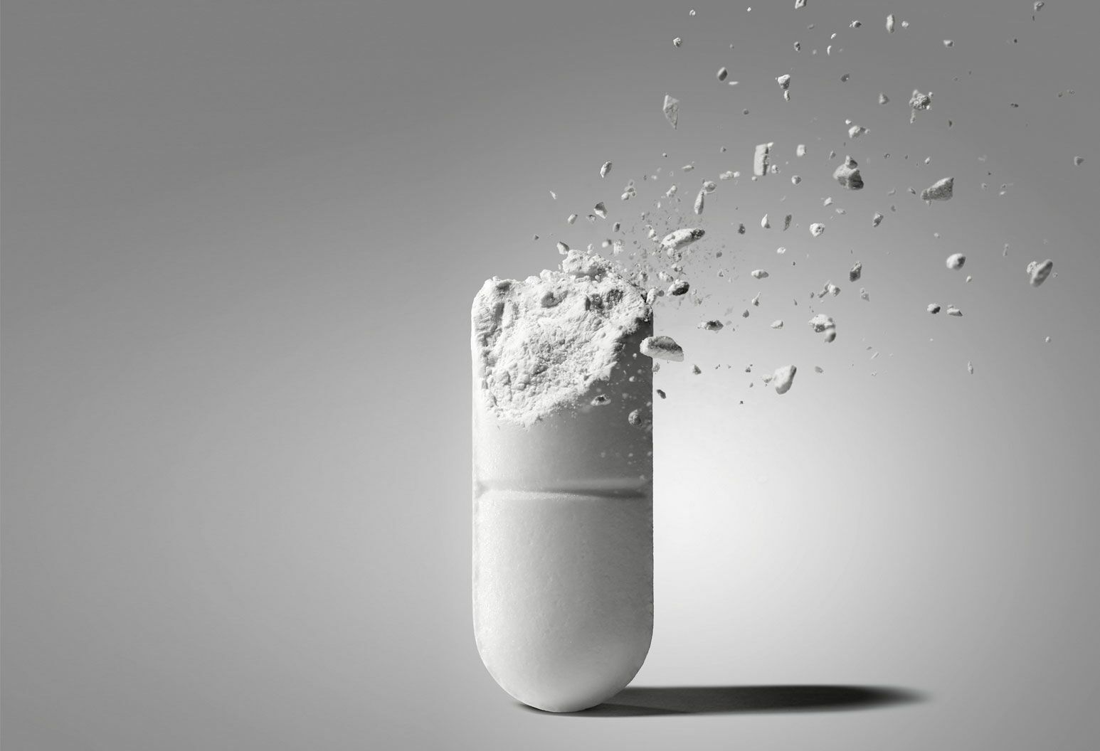 The top half of a white pill is being shattered apart and floating away against a grey background.