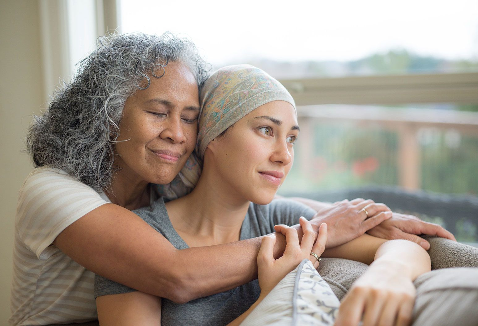 An older woman with grey hair gives a comforting hug from behind of a younger woman sitting on a couch. The younger woman is wearing a bandana to cover her hair and looks out the window.