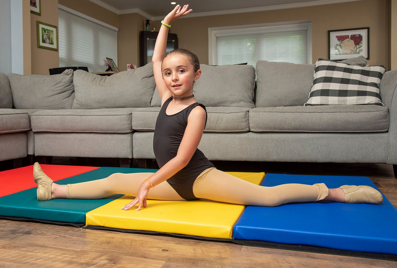Young girl in black leotard doing a split on a gymnastics mat in her home.
