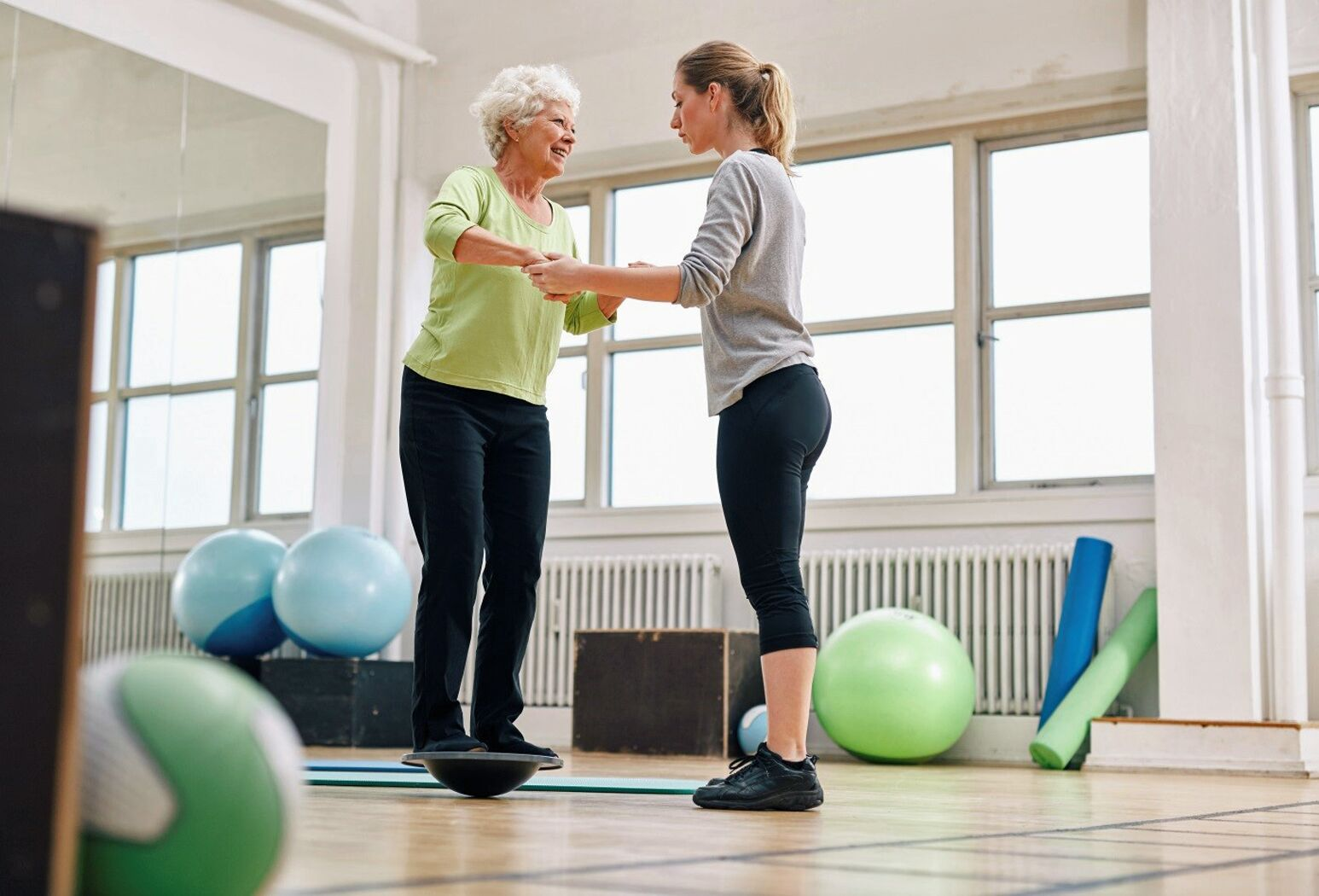 A physical therapist works with an elderly woman. Chris Kudlik, PT, DPT, highlights the benefits of vestibular rehabilitation for those recovering from brain trauma.