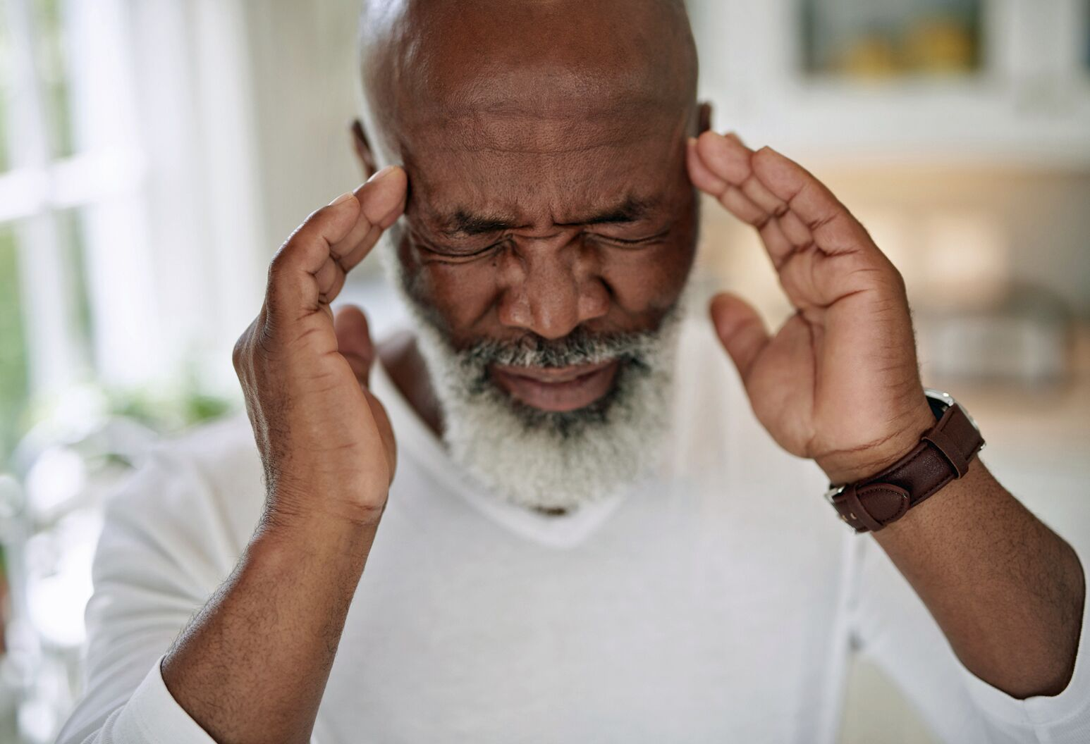 A elderly black man holds his head in pain
