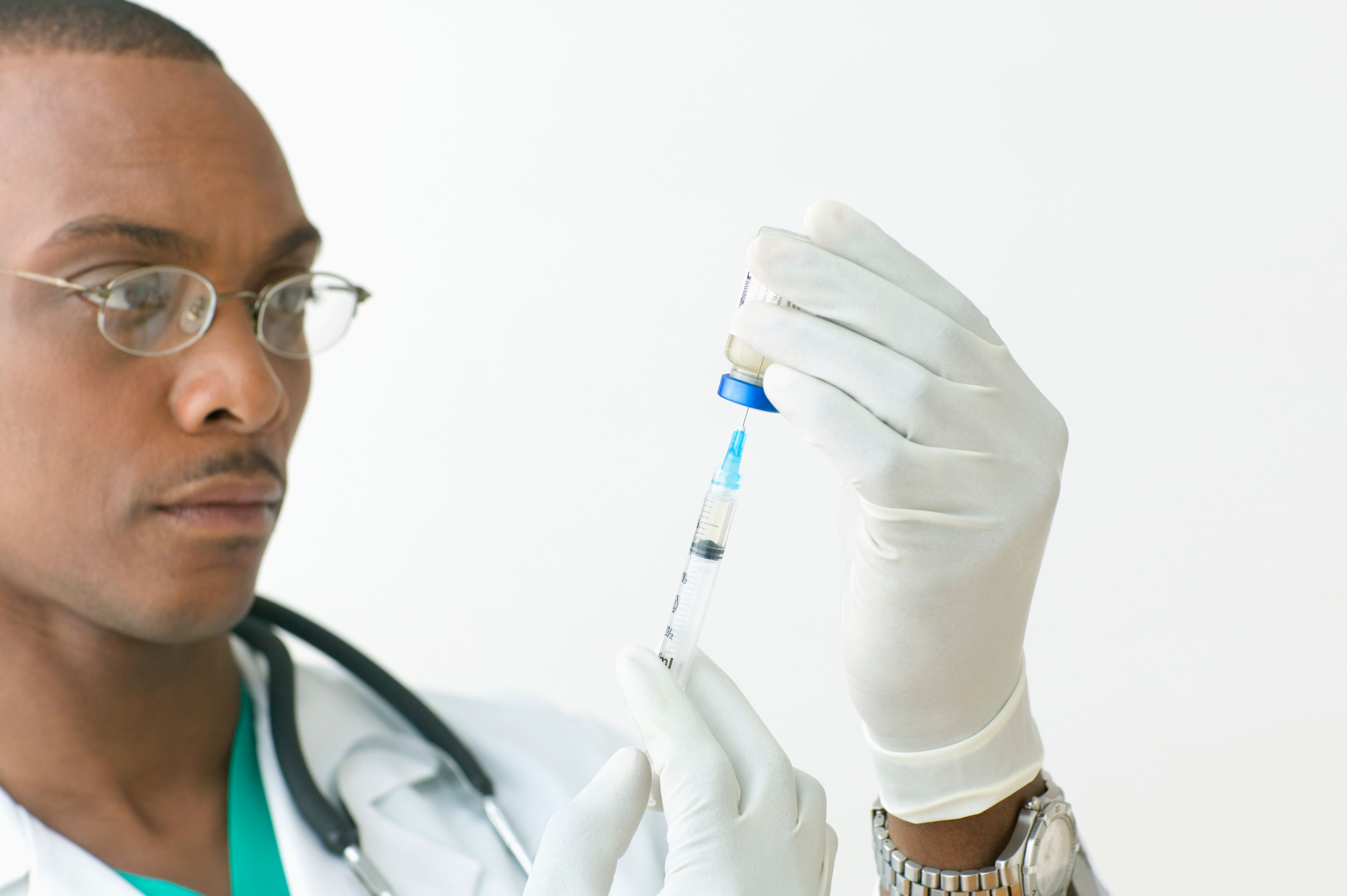 A doctor fills a needle with a vaccination