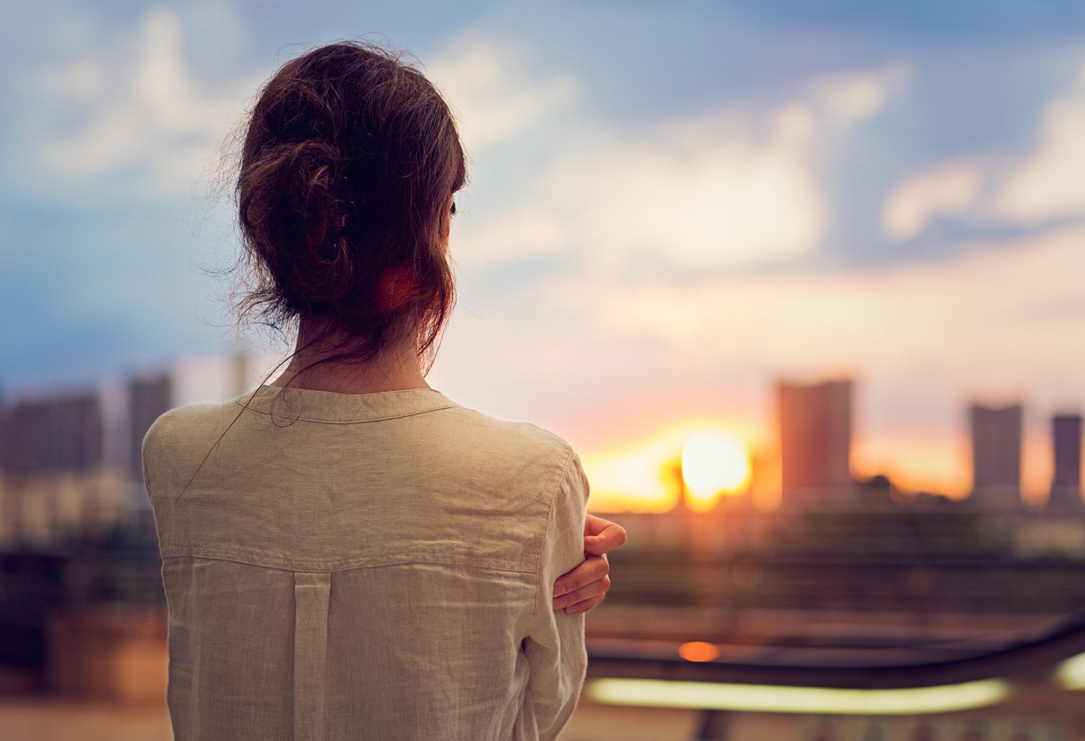 This is an image of a woman with her back to the camera, hair in a messy bun, with her arms crossed in front of her chest, looking off into the distance at a sunset.