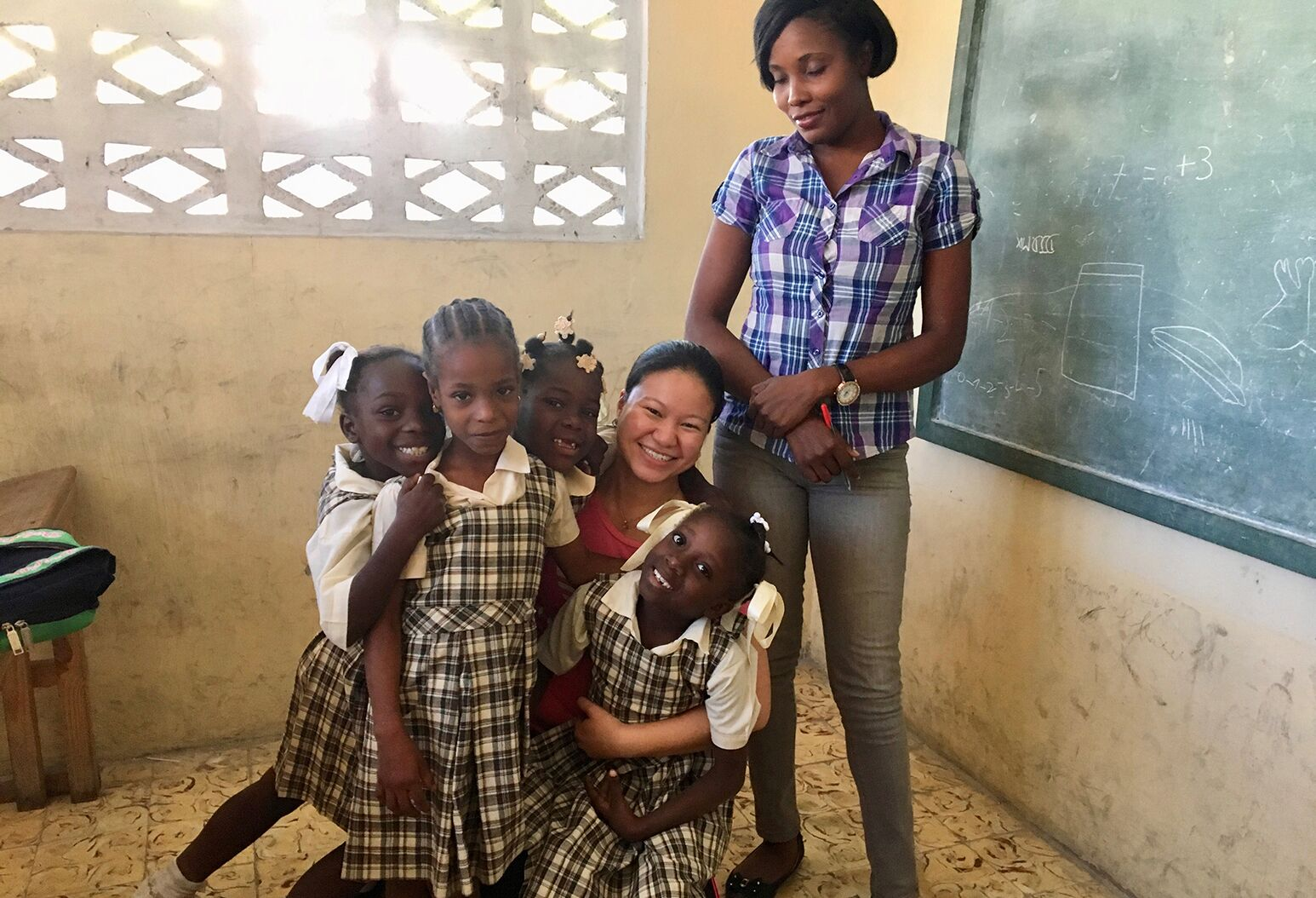 Nina Ng hugs a group of smiling Haitian children in a classroom while their schoolteacher stands nearby.