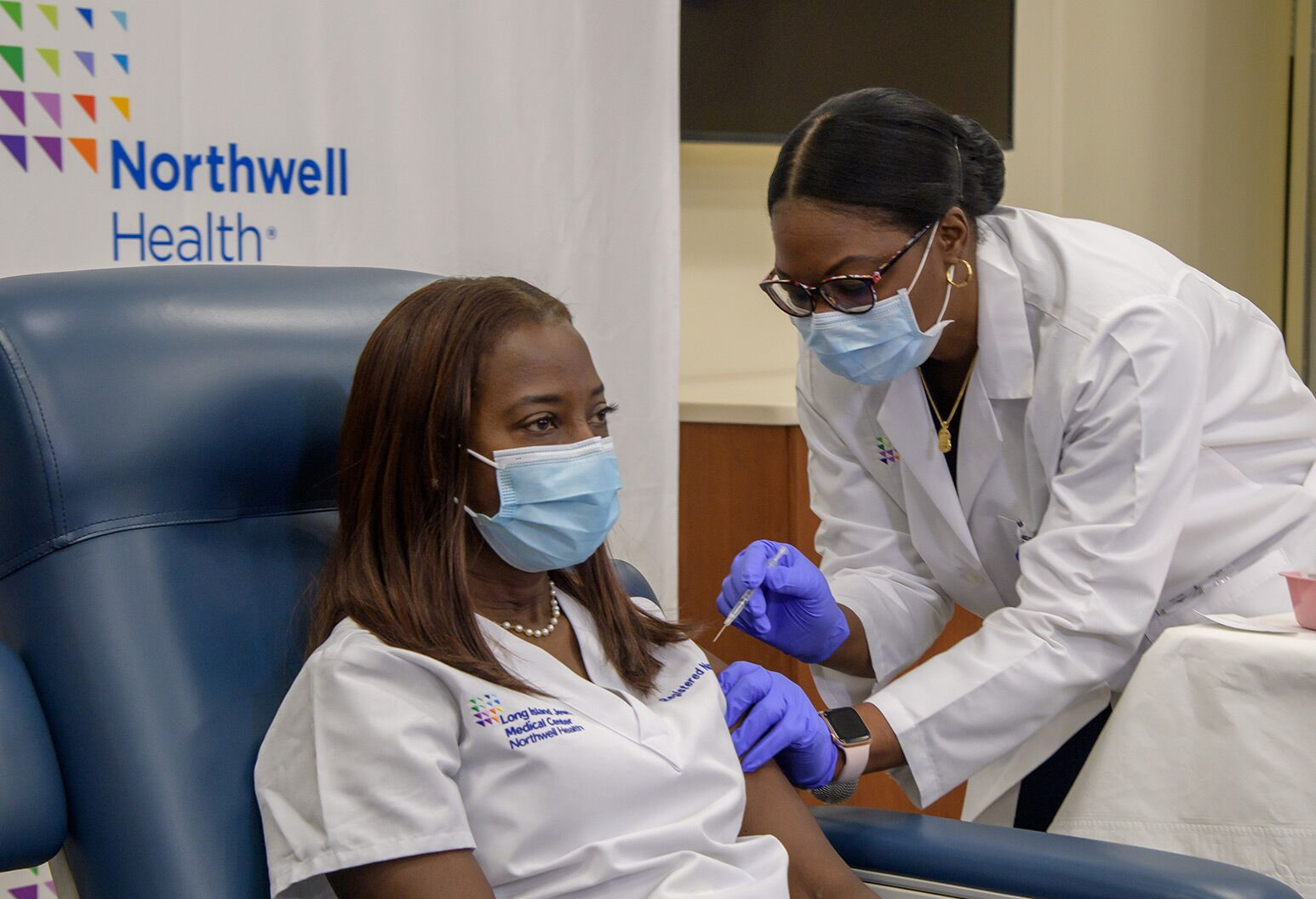 African American woman in mask and scrubs sits in chair as another African American woman in mask and lab coat holds a syringe
