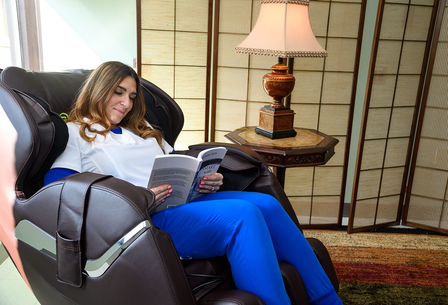 Glen Cove Hospital nurse, Andrea Marchese, RN, relaxes in an electric massage chair.