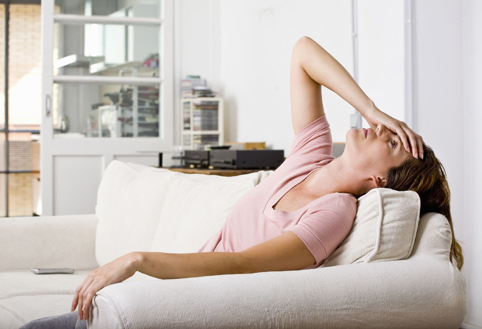 woman on couch holding her aching head