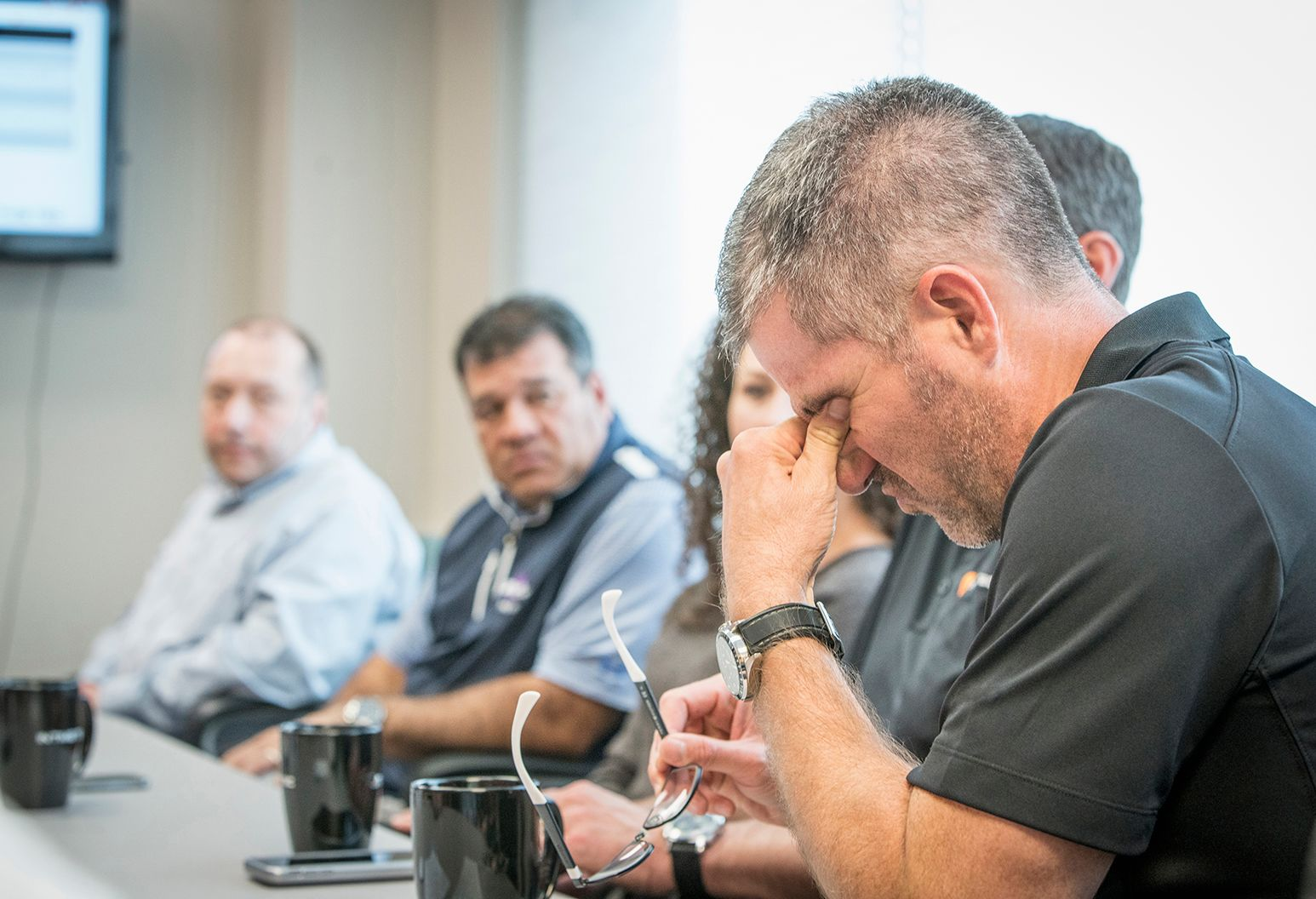 Man struggling to stay awake during a meeting