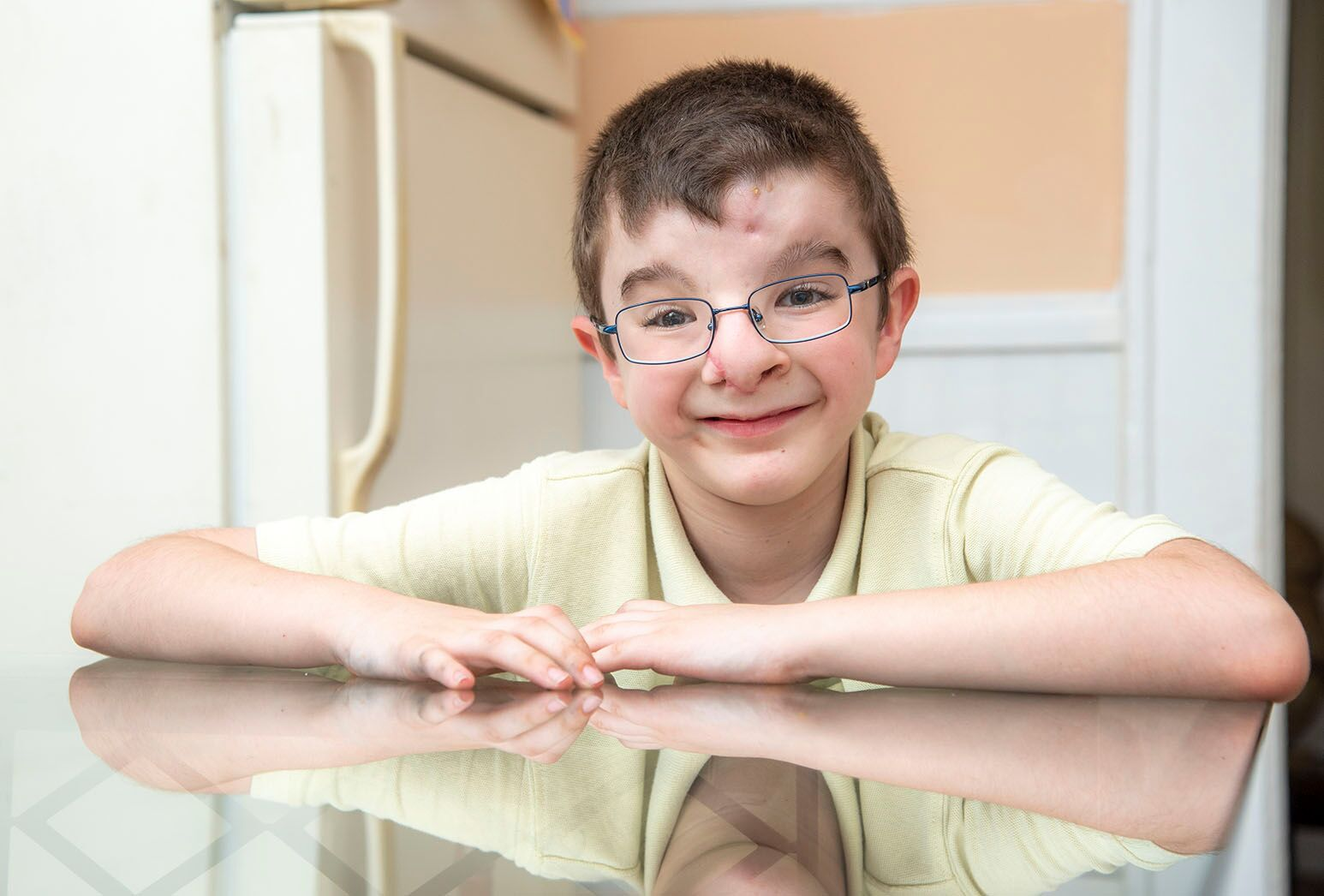 Young boy with dark hair and glasses sits smiling at a glass-topped kitchen table.