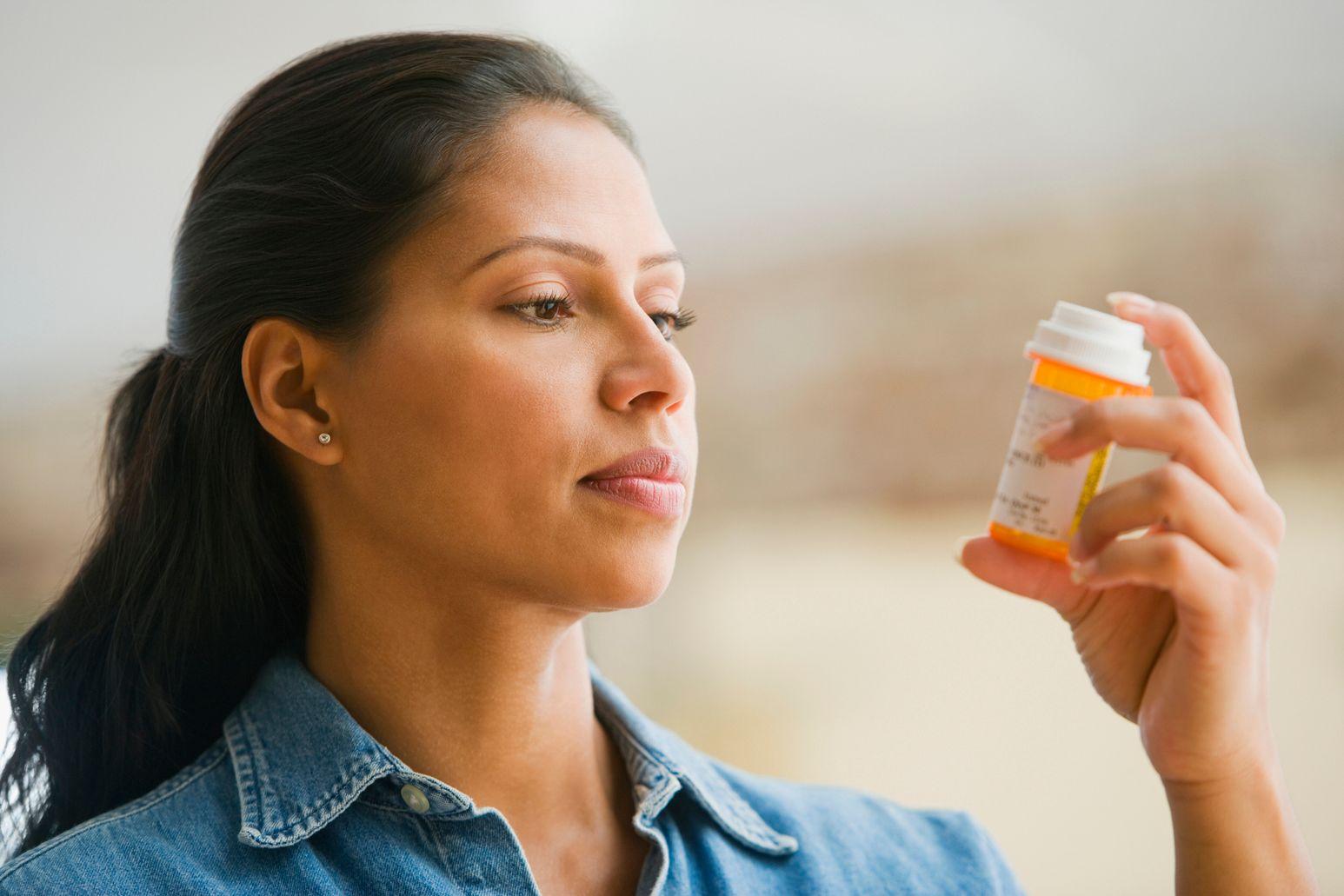 A woman looks at a prescription bottle