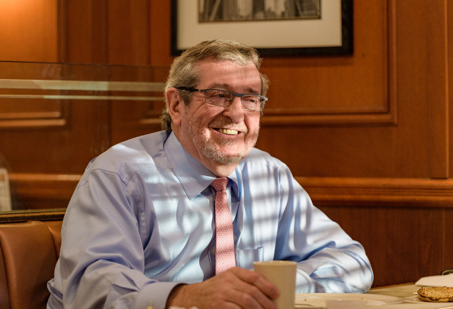 Michael Dowling smiling as he sits at his desk.