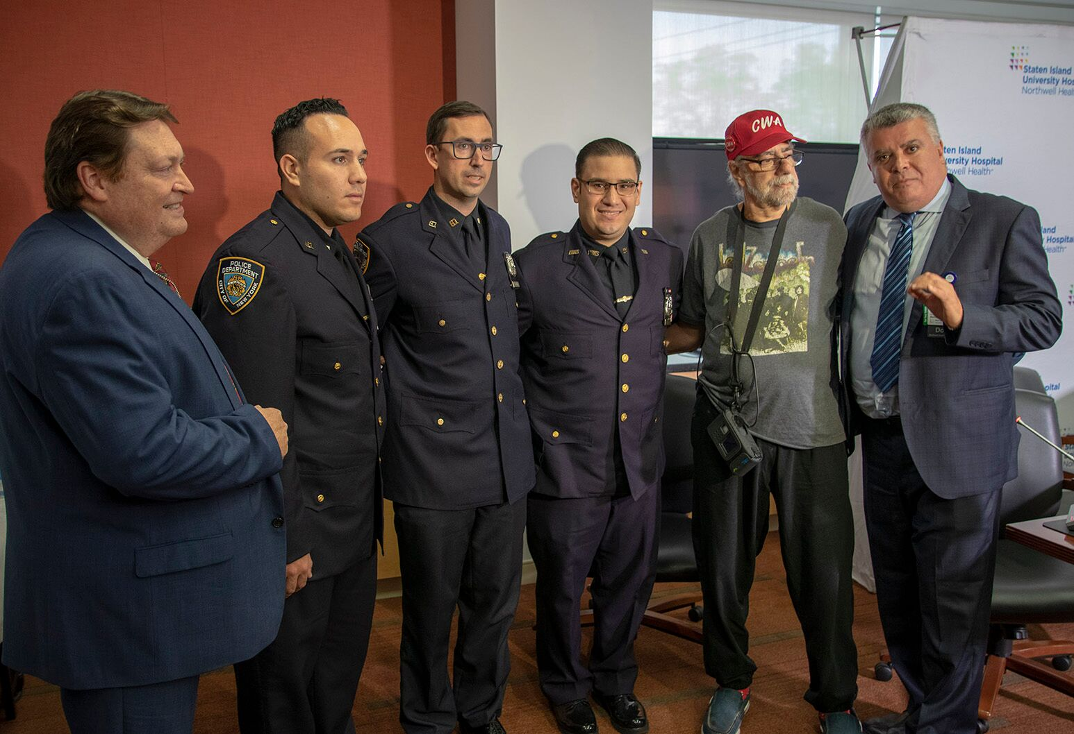 Roy Spiro (red hat) stands with his NYPD and cardiac surgery lifesavers at Staten Island University Hospital.