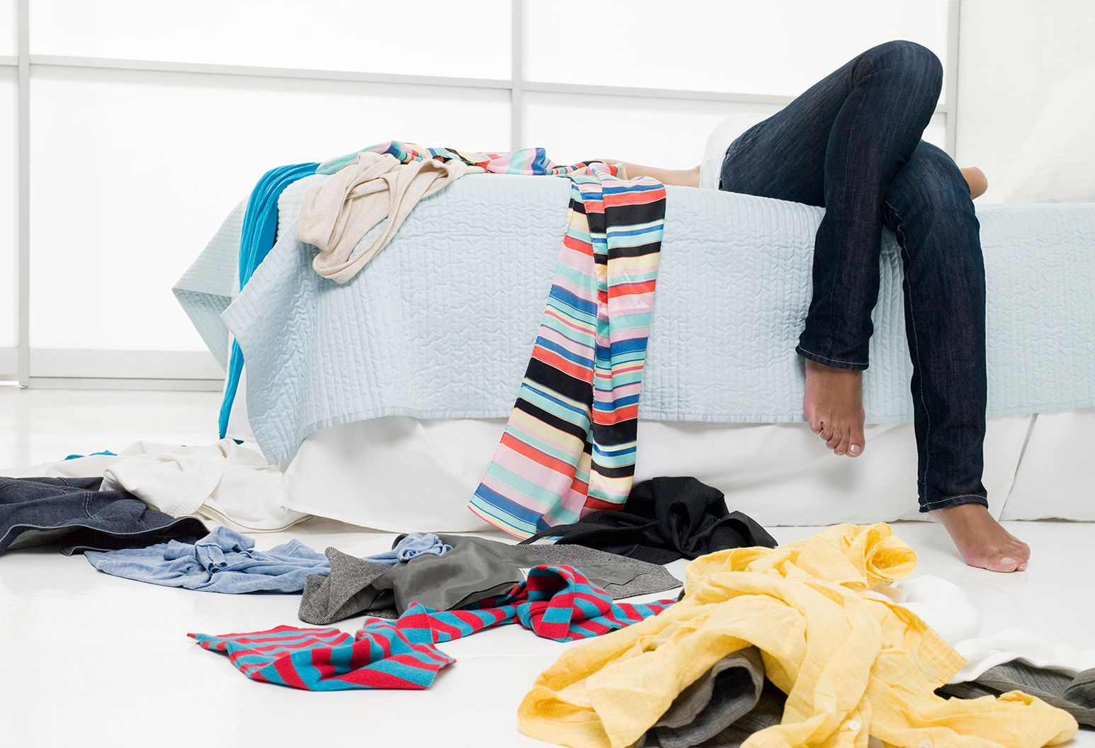 Two legs dangle over the edge of a white bed with a light blue comforter. There are colorful clothes everywhere strewn about the bed and floor.