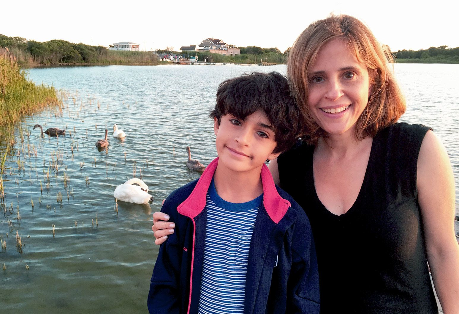 a young boy with curly black hair, a striped shirt displays a faint smile as he stands in front of a lake with an older woman with her hand on his shoulder. She has shoulder length auburn hair, and wears a black top. In the lake are geese treading in the water as the sun begins to set.