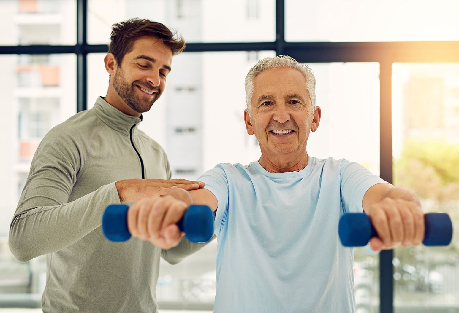 Portrait of a friendly physiotherapist helping his senior patient work out with weights