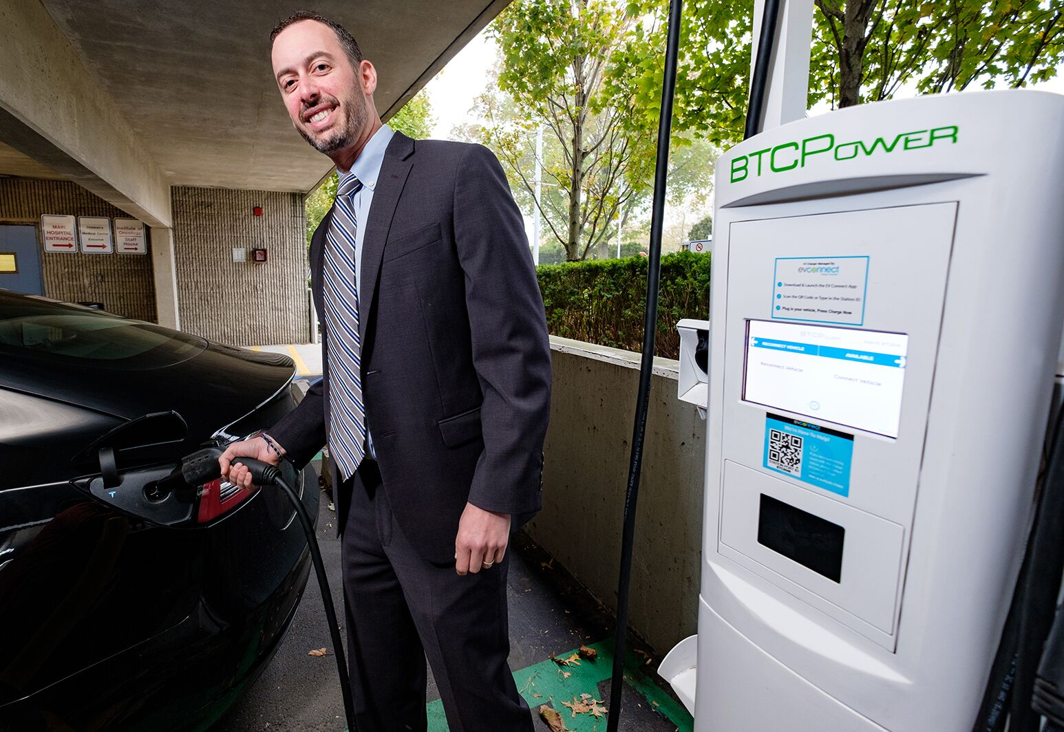 Long Island Jewish Medical Center Executive Director Michael Goldberg plugs in an electric car at one of the hospital's electric vehicle charging stations.