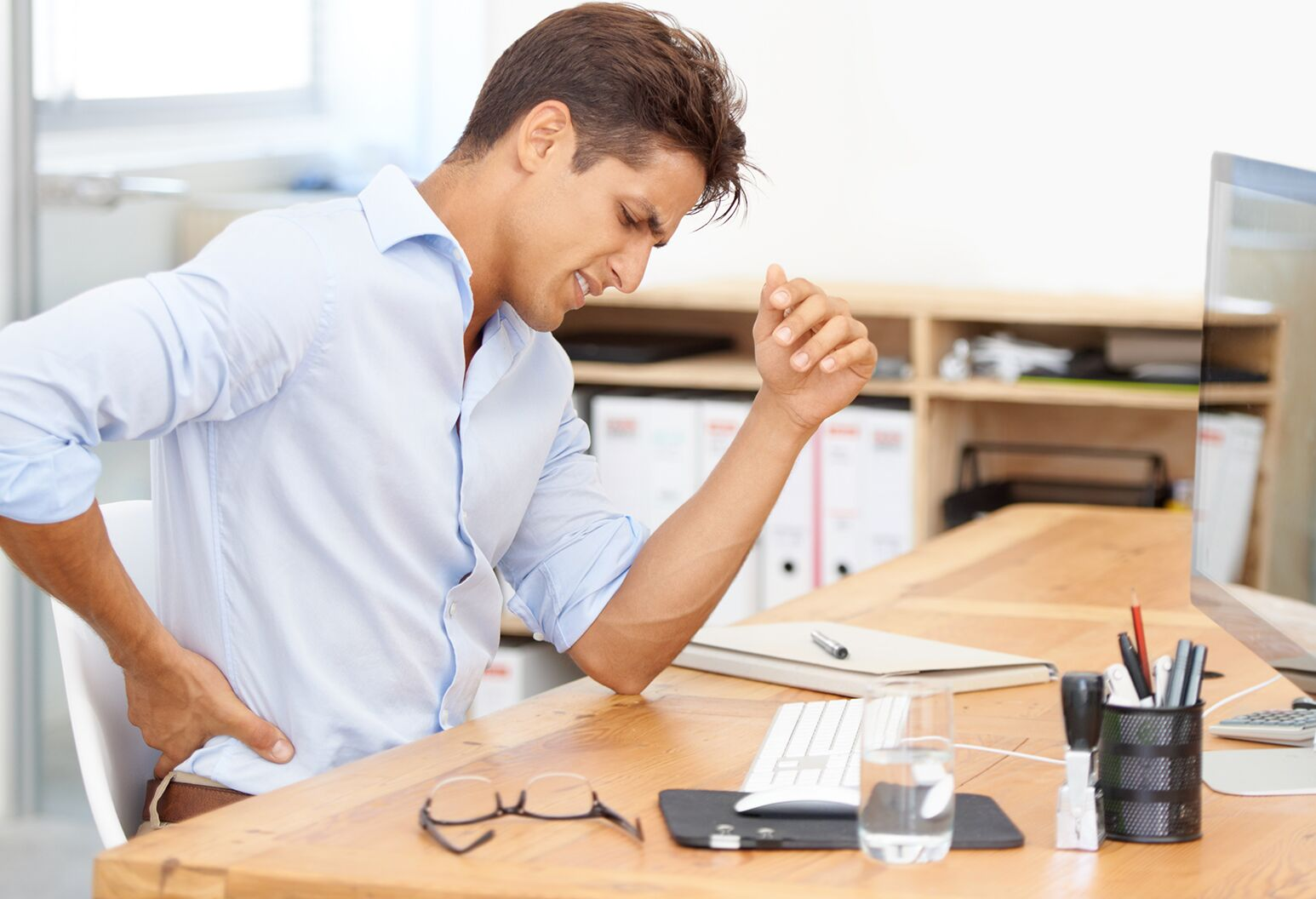 businessman rubbing his aching back while sitting at his desk in front of his computer
