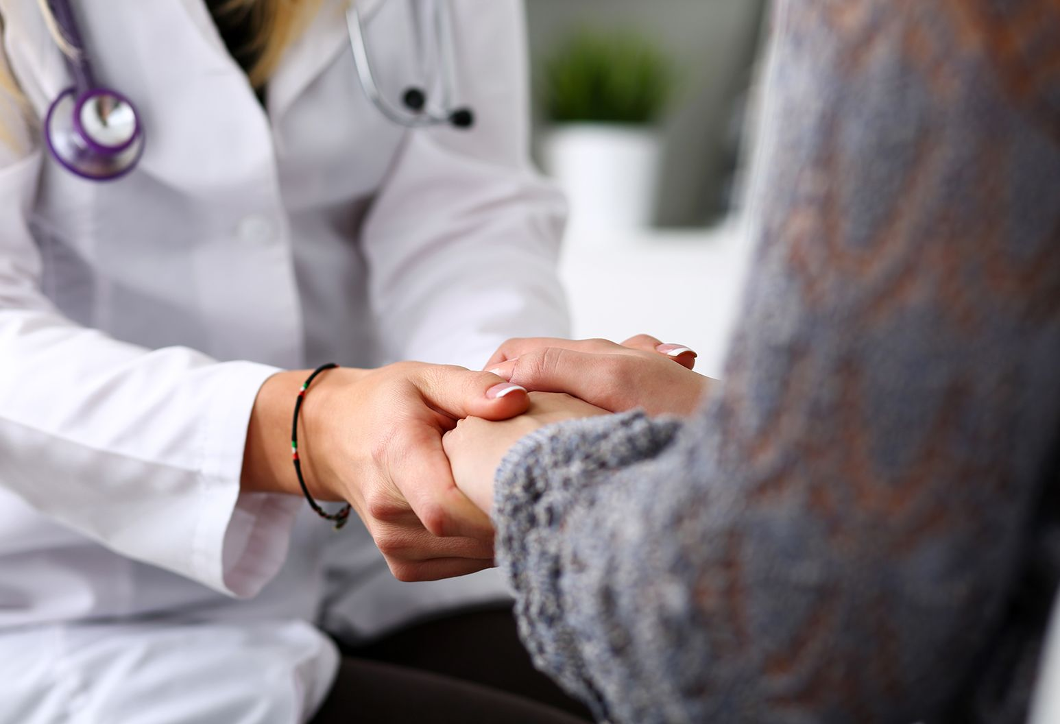 With only hands visible, female doctor with white lab coat and stethoscope is shown holding hands with female patient.