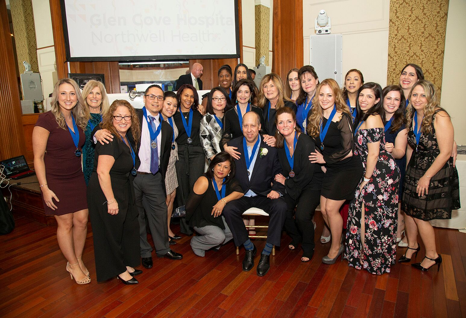 A group of smiling people wearing blue ribbon medals surround a man who is sitting in the middle. Image Caption: Jay's whole team came out to honor him at Glen Cove Hospital's Heroes Night.