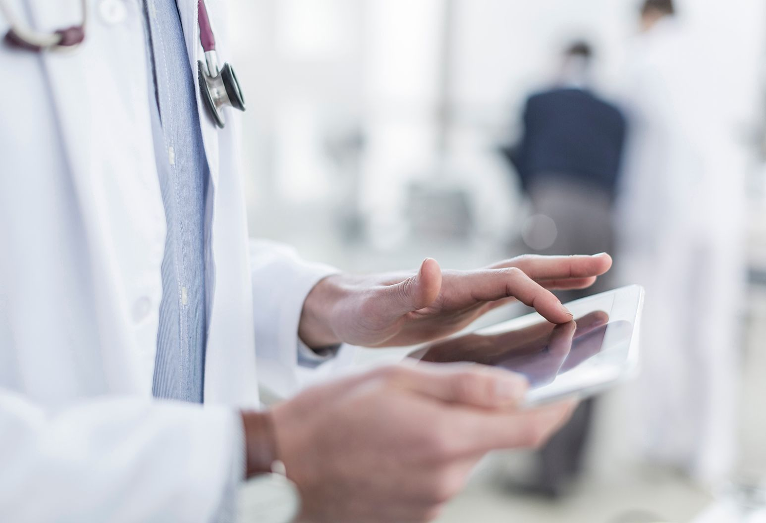Close-up of a doctor's hands using a white tablet. He is in a white coat and wears a stethoscope.
