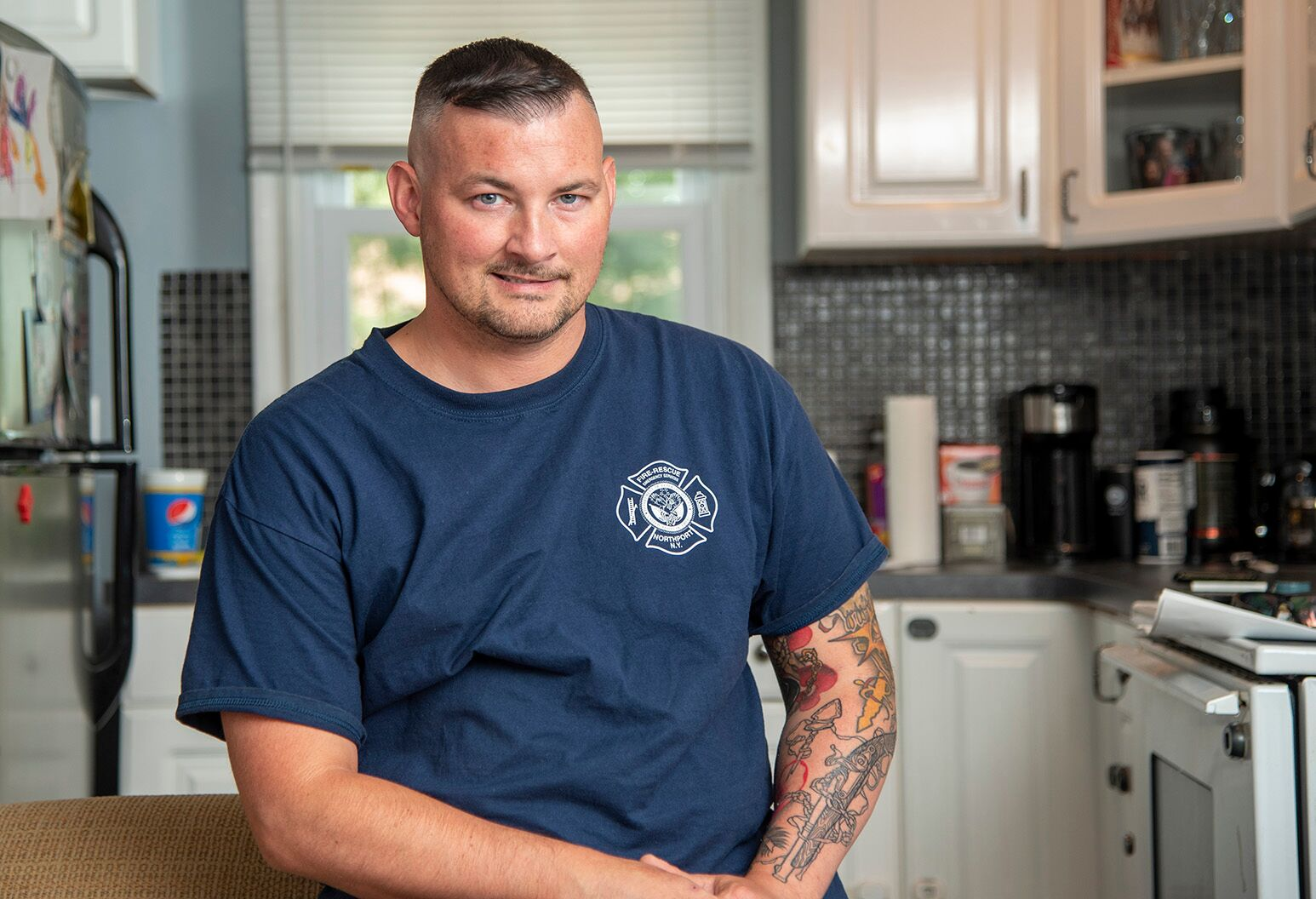 A man with tattoos wearing a navy t-shirt with a firefighter logo smiles in his kitchen.