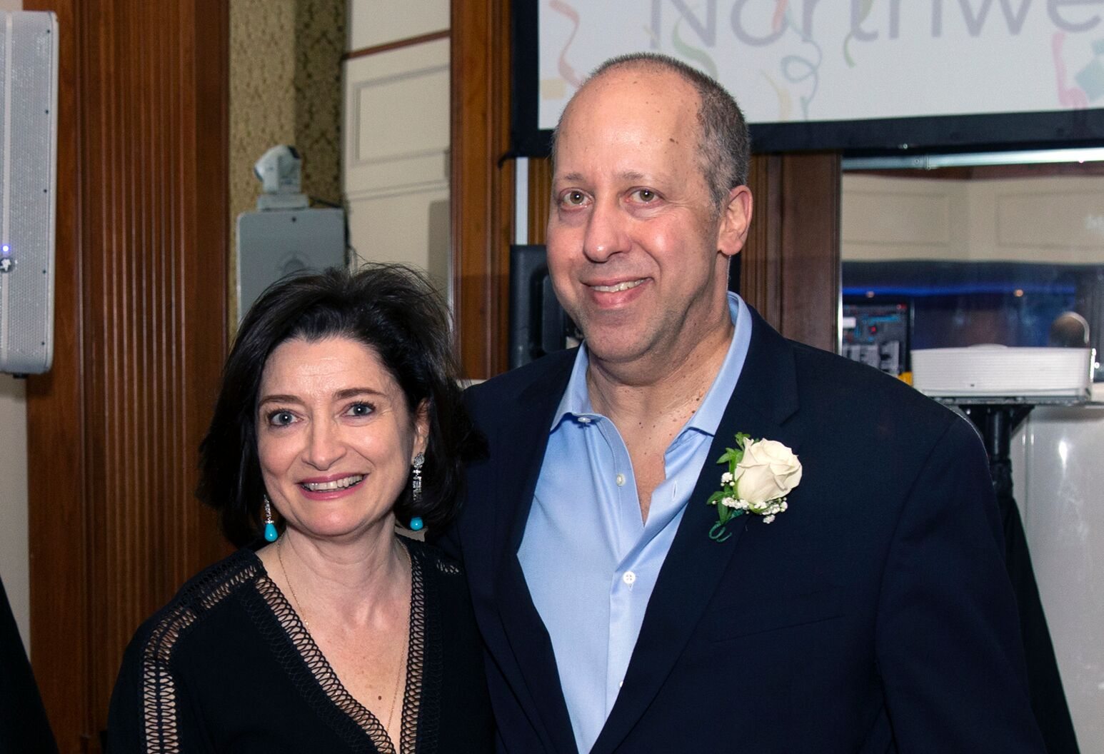 Older woman and man in formal attire standing together arm-in-arm.