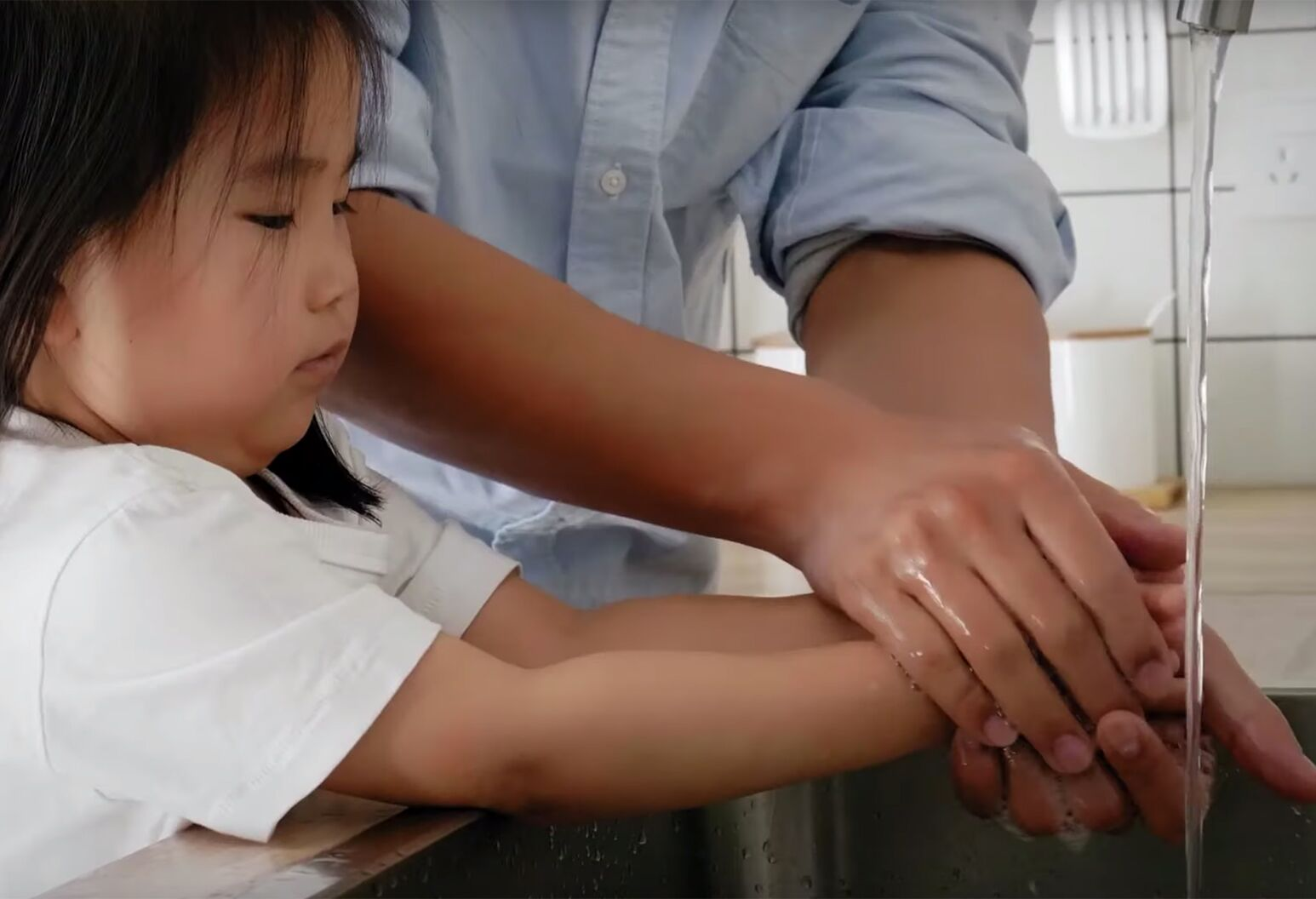 A little girl stands at a kitchen sink washing her hands, while a parent holds her hands and helps her.