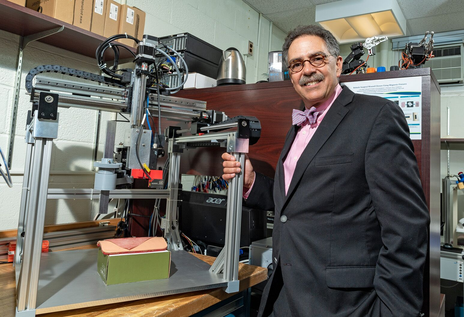 Louis Kavoussi stands next to his surgical suturing device
